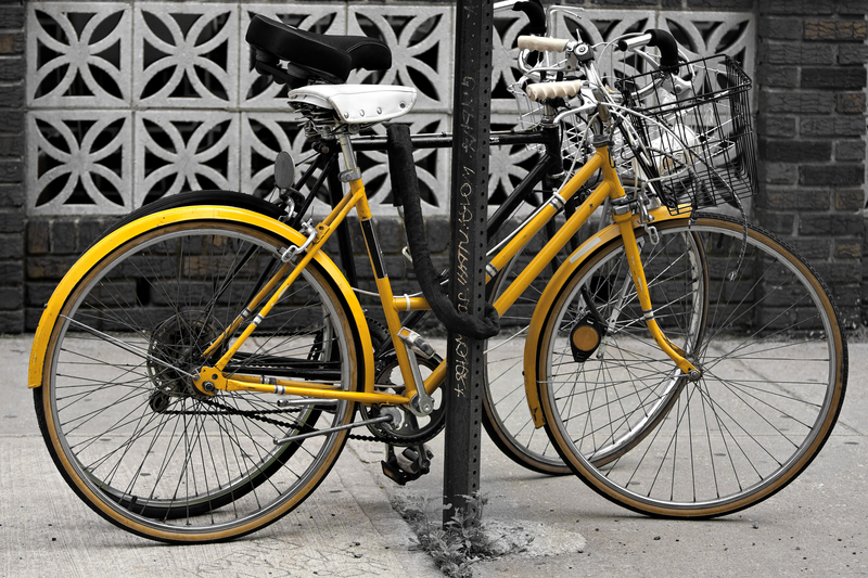 A couple of bicycles chained to a post in the city selective color with highlight on the yellow hfwozorhj